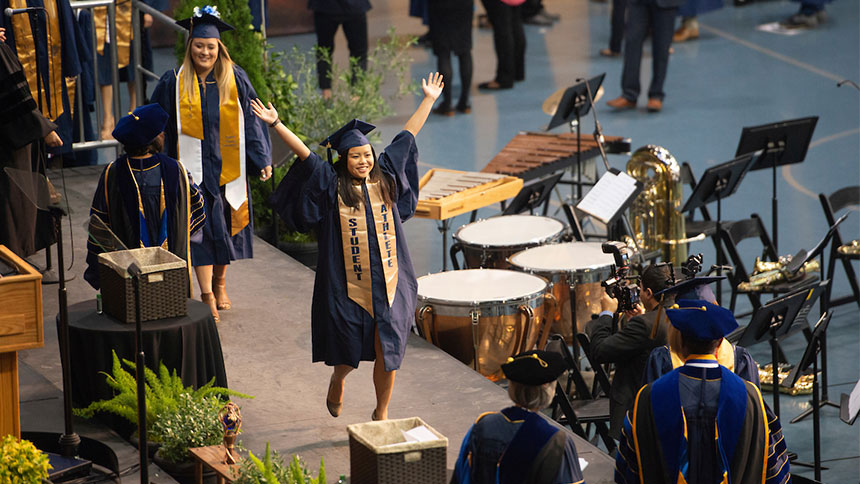 A graduate raises her arms as she crosses a graduation stage