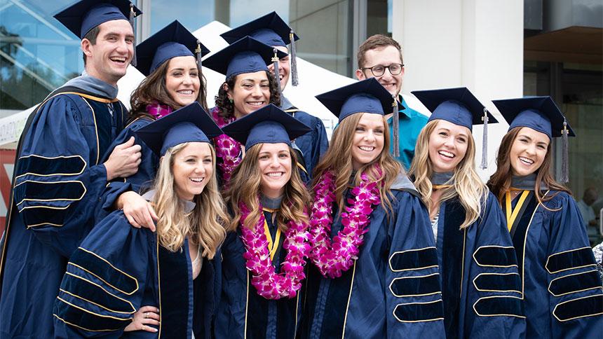 Ten happy graduates pose for a photograph