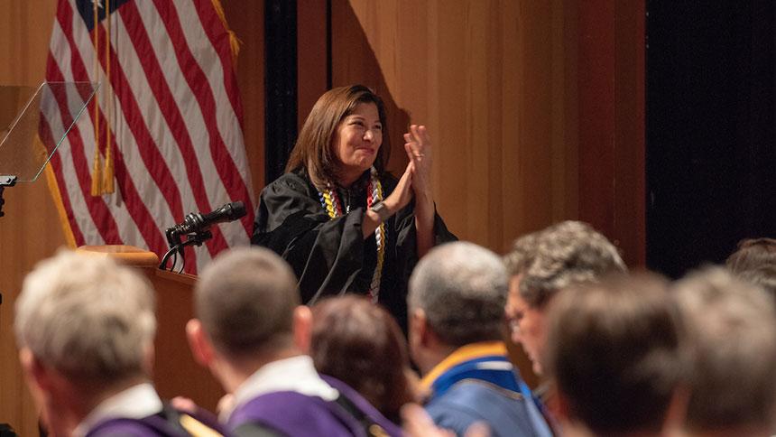 Woman speaker applauds graduates at School of Law commencement
